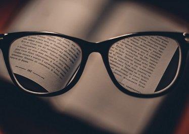 okulary na tle tekstu książki
