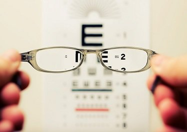 okulary na tle tablicy z literami